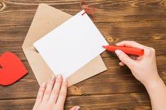 Sobre del papel de Kraft con el corazón rojo de madera en la tabla de madera con Imagenes de archivo