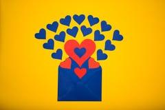 Sobre del saludo con los corazones de papel en fondo amarillo Los corazones vierten fuera del sobre Los corazones vuelan hacia fu Imagenes de archivo
