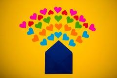 Sobre del saludo con los corazones de papel en fondo amarillo Los corazones vierten fuera del sobre Los corazones vuelan hacia fu Foto de archivo libre de regalías