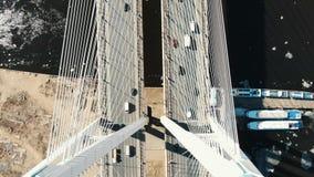 Sobre el puente cable-permanecido sobre el río son los camiones y los coches, visión aérea almacen de video