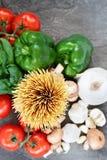 Sobre el tiro de espaguetis y de ingredientes crudos para la salsa Foto de archivo