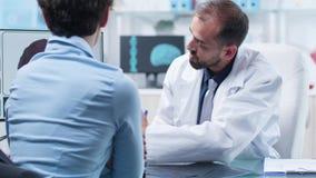 Sobre el tiro del hombro del científico médico que muestra al paciente una simulación del cerebro 3D almacen de video