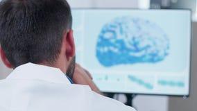 Sobre el tiro del hombro de la cabeza del doctor que mira la simulación del cerebro 3D almacen de metraje de vídeo