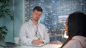 Sobre - el tiro del hombro Psicólogo de sexo masculino en capa del laboratorio que escucha el paciente y que hace notas metrajes