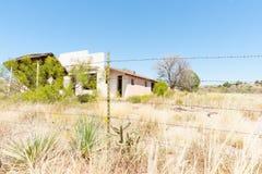 Sobre la cerca construcción abandonada demasiado grande para su edad más allá del alambre de púas f Fotografía de archivo libre de regalías