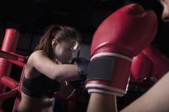 Sobre la opinión del hombro dos boxeadores de sexo femenino que encajonan en el ring de boxeo en Pekín, China Foto de archivo libre de regalías