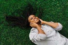 Sobre la opinión el adolescente afroamericano alegre que escucha la música mientras que pone en la hierba Imagen de archivo libre de regalías