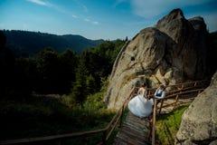 Sobre la opinión la novia del encanto que va abajo de las escaleras de madera al novio rubio Ubicación de las montañas Naturaleza Foto de archivo libre de regalías