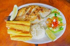 Sobre la opinión pescados fritos sirvió con la ensalada, el arroz, y la yuca laterales servida en una placa blanca sobre una tabl Imagen de archivo