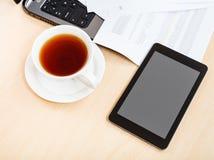 Sobre la taza de la visión de PC del té y de la tableta en el escritorio Imagen de archivo libre de regalías