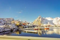Sobre la vista de algunos edificios de madera en la bahía con los barcos en la orilla en las islas de Lofoten rodeadas con nevoso Imagen de archivo libre de regalías