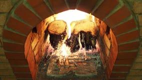 Sobre la vista de los tocones de madera que queman en el hogar de la chimenea almacen de metraje de vídeo