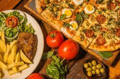 Sobre la vista del grupo de comida rápida, de potatos asados a la parrilla de la carne de vaca, de la pizza y de la fritada, con  Imágenes de archivo libres de regalías