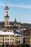 Sobre las casas europeas en la vieja parte de Lviv sube la torre de Hall Lviv de la ciudad y la iglesia de Dormition en día de in Fotografía de archivo libre de regalías