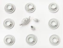 Sobre las tazas de la visión con los platillos y la tetera en blanco Foto de archivo libre de regalías