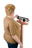 Sobre o olhar do ombro em uma mulher que verific seu peso Fotografia de Stock