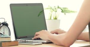 Sobre o ombro disparou de uma mulher asiática que datilografa em um laptop com uma tela verde chave filme