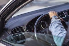 Sobre - o tiro do ombro de um homem novo que guarda o volante do carro foto de stock