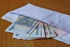 Sobre por completo de la rublo rusa de la moneda rusa, de la FROTACIÓN como símbolo de la transferencia del efectivo, del blanque Foto de archivo