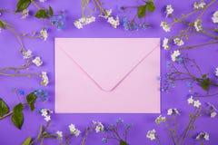 Sobre rosado rodeado con las pequeñas flores azules y blancas en el fondo violeta Imágenes de archivo libres de regalías