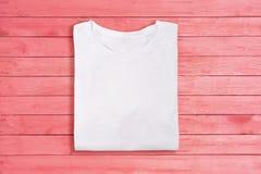 Sobre vista de la camiseta en blanco doblada blanca en fondo de madera rosado Plantilla femenina del diseño de la camiseta fotos de archivo libres de regalías