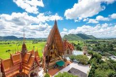 Sobre vista de la iglesia de oro con el campo grande de la estatua y del arroz de Buda Foto de archivo