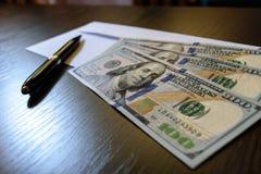 Sobre y 100 billetes de banco del dólar de EE. UU. Fotografía de archivo