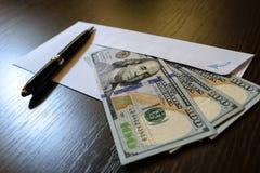 Sobre y 100 billetes de banco del dólar de EE. UU. Imagen de archivo libre de regalías