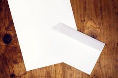 Sobre y documento blancos en blanco sobre el escritorio de madera Fotos de archivo libres de regalías