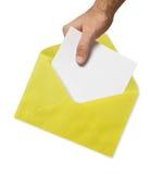 Sobre y mano amarillos Fotos de archivo libres de regalías