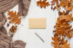Sobre y pluma sin firmar en la tabla de madera blanca con los accesorios del otoño Visión desde arriba Fotos de archivo