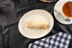 Sobremesa caseiro do eclair com molho da baunilha na placa branca com o copo do chá na tabela imagens de stock