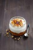 A sobremesa com creme, o granola e o pêssego bloqueiam, vertical Foto de Stock Royalty Free