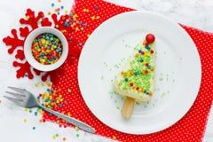 Sobremesa da árvore de Natal - o bolo de queijo da parcela na vara com açúcar colorido polvilha a árvore de Natal dada forma imagem de stock