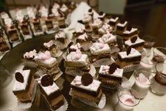 A sobremesa da variedade do casamento endurece com cor saboroso do bufete decorada com creme do chocolate e as cerejas chicoteado Imagens de Stock