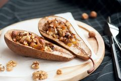 Sobremesa das peras cozidas com mel e porcas em uma placa de madeira Fotografia de Stock Royalty Free