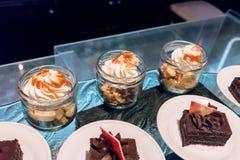 A sobremesa de Banoffee nos frascos de vidro cobriu com creme de chicoteamento avante foto de stock royalty free