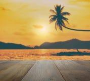 Sobremesa de madera con el árbol de coco borroso que cuelga sobre la playa tropical en la puesta del sol Fotografía de archivo