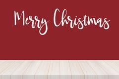Sobremesa de madera con la fuente de la Feliz Navidad en fondo rojo fotos de archivo libres de regalías