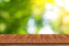 Sobremesa de madera en fondo del verde del extracto del bokeh Imágenes de archivo libres de regalías