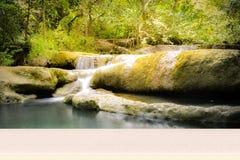 Sobremesa de madera en la cascada ocultada en la selva tropical imagenes de archivo