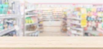 Sobremesa de madera vacía con el fondo defocused borroso colmado del supermercado imágenes de archivo libres de regalías