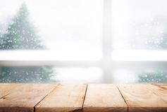 Sobremesa de madera vacía en la opinión de la ventana de la falta de definición con el árbol de pino en nieve fotos de archivo