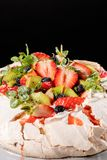 Sobremesa do bolo da merengue de Pavlova feita com morangos, quivi, mirtilos e hortelã fotografia de stock