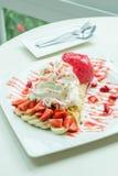 Sobremesa do crepe da morango do gelado na tabela de madeira do prato branco em c foto de stock