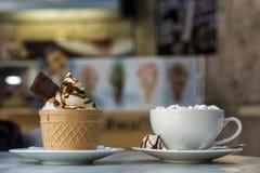 Sobremesa do gelado no copo da bolacha com cookies do chocolate e e caneca de caf? com os marshmallows na placa da porcelana no b fotografia de stock