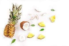 Sobremesa do verão com abacaxis e coco na opinião superior do fundo branco Imagem de Stock Royalty Free
