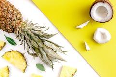 Sobremesa do verão com abacaxis e coco na opinião superior do fundo colorido Imagens de Stock