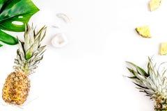 Sobremesa do verão com abacaxis e folhas na zombaria branca da opinião superior do fundo acima Foto de Stock