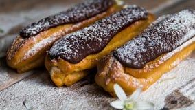 Sobremesa francesa tradicional Eclair com crosta de gelo do chocolate no açúcar pulverizado vídeos de arquivo